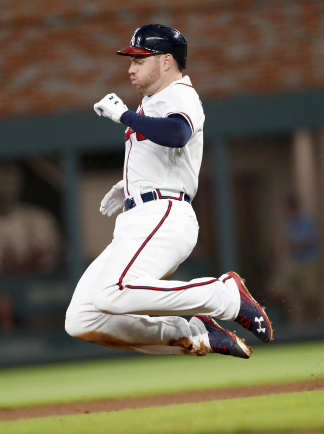 Atlanta Braves' Freddie Freeman (5) slides into second base after a fielding error by Cincinnati Reds first baseman Joey Votto in the seventh Inning of a baseball game Tuesday, June 26, 2018, in Atlanta. The Braves won 5-4 in 11 innings. (AP Photo/John Bazemore)