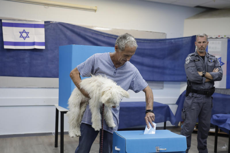 FILE - In this Tuesday, Sept. 17, 2019 file photo, a man votes at a polling station in Rosh Haayin, Israel. In Israel's secular heartland, the role of religion in daily life played a central role in this week's deadlocked election. For many, a vote for the opposition was driven by a desire to keep rabbis out of their schools, businesses and love lives. (AP Photo/Sebastian Scheiner, File)
