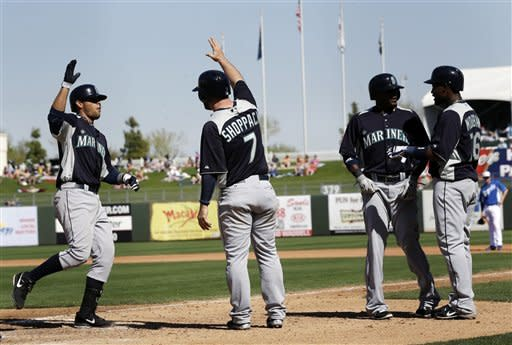 Seattle Mariners' Stefen Romero, left, celebrates his grand slam with teammate Kelly Shoppach (7) against the Kansas City Royals during the fourth inning of an exhibition spring training baseball game on Thursday, March 7, 2013, in Surprise, Ariz. (AP Photo/Marcio Jose Sanchez)