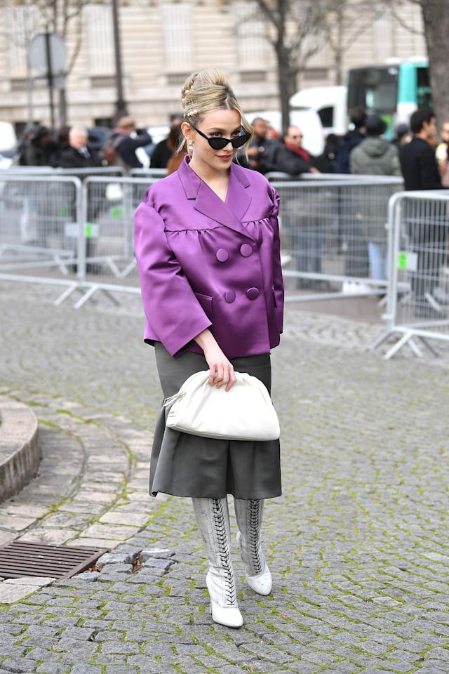 "<p><a href=""https://www.elle.com/uk/life-and-culture/culture/a30527528/you-season-3-netflix/"" target=""_blank"">The You actor</a> attended the Miu Miu show during Paris Fashion Week wearing an oversized boxy purple jacket, a grey midi skirt, white boots and cat eye sunglasses.</p>"