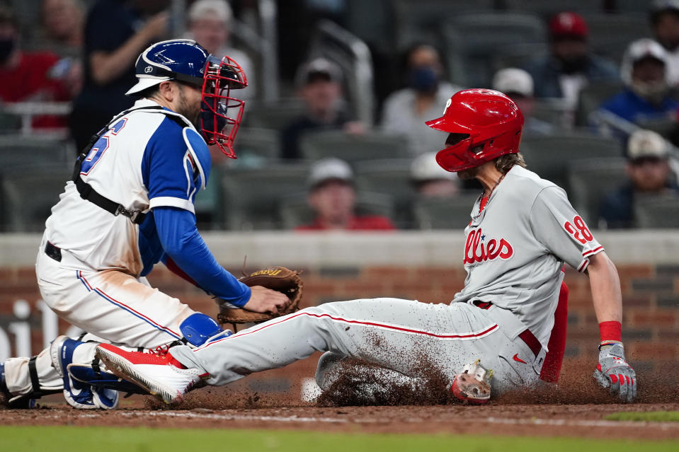 Philadelphia Phillies' Alec Bohm (28) beats the tag from Atlanta Braves catcher Travis d'Arnaud (16) to score the winning run on a Didi Gregorius sacrifice fly in the ninth inning of a baseball game Sunday, April 11, 2021, in Atlanta. (AP Photo/John Bazemore)