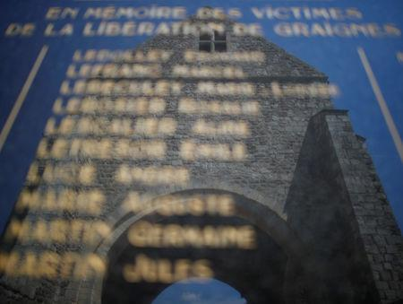 Remains of the former church are reflected in the villages war monument in Graignes, France May 15, 2019. Picture taken May 15, 2019. REUTERS/Christian Hartmann