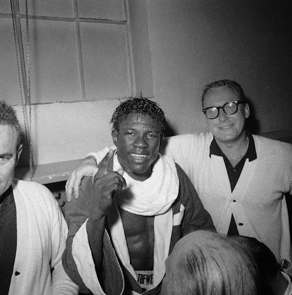FILE - In this June 8, 1963 file photo, Emile Griffith smiles in the dressing room after regaining his welterweight world championship title by defeating Luis Rodriguez, at New York's Madison Square Garden. At right is Griffith's coach Gil Clancy. The International Boxing Hall of Fame says former world champion boxer Emile Griffith has died. He was 75. The hall said Tuesday, July 23, 2013, he died at an extended care facility in Hempstead, N.Y.(AP Photo/File)