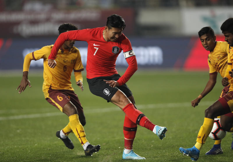 South Korea's Son Heung-min, center, kicks the ball past Sri Lanka's Mohamed Aman, left, during their Asian zone Group H qualifying soccer match for the 2022 World Cup at Hwaseong Sports Complex Main Stadium in Hwaseong, South Korea, Thursday, Oct. 10, 2019. (AP Photo/Lee Jin-man)