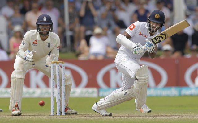 Sri Lanka's Dimuth Karunaratne plays a shot as England's Ben Foakes watches during the fourth day of the first test cricket match between Sri Lanka and England in Galle, Sri Lanka, Friday, Nov. 9, 2018. (AP Photo/Eranga Jayawardena)