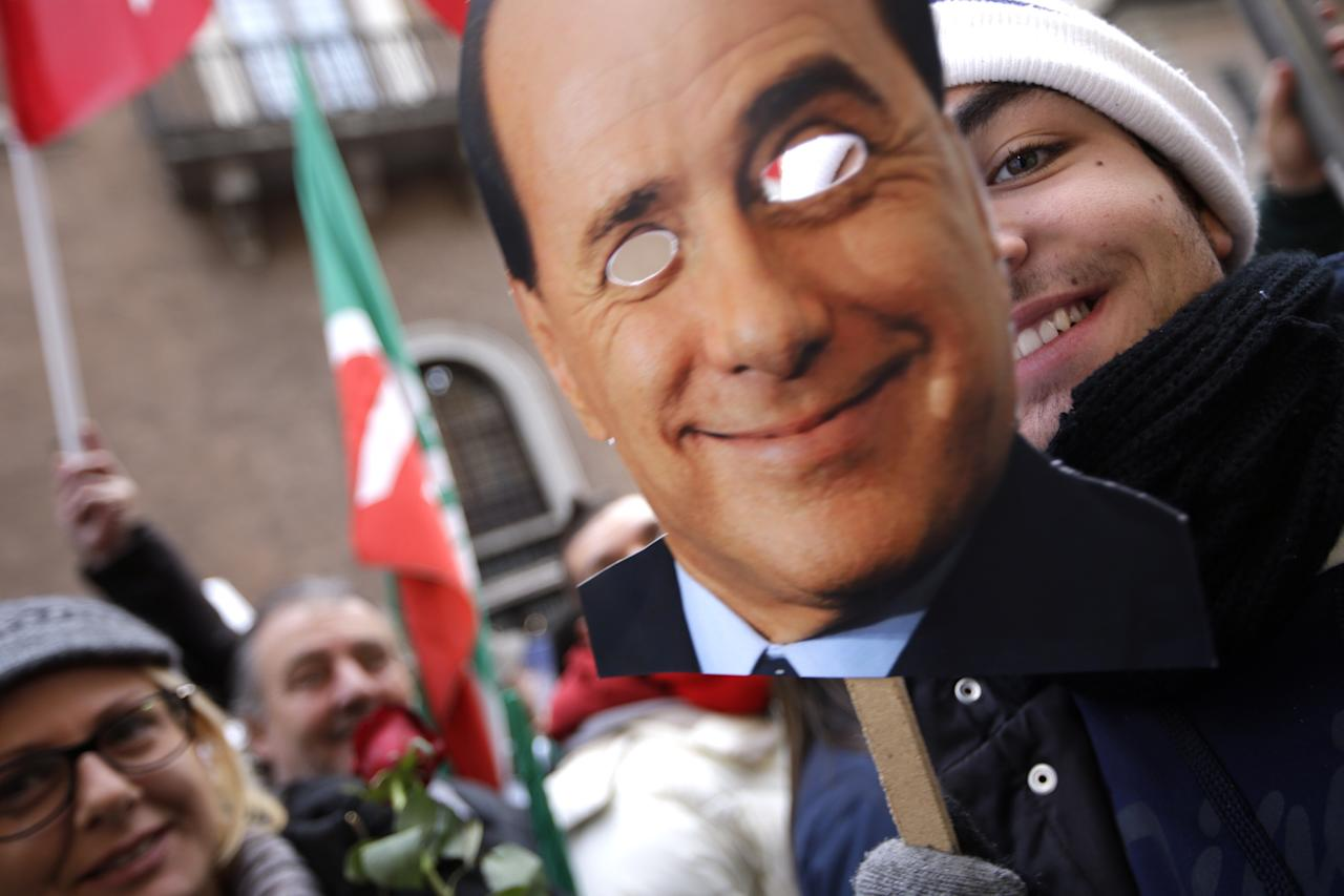 A supporter uses a cut out photoraph of Italian Premier Silvio Berlusconi as a mask while he waits for Berlusconi's speech at a rally organized outside of his Rome residence, Wednesday, Nov. 27, 2013. The Italian Senate has begun debating whether to kick Silvio Berlusconi out of Parliament following his tax fraud conviction. The vote is scheduled later in the day and most analysts expect he will lose his seat. Berlusconi fans massed in front of his Rome palazzo for a planned rally that analysts say is essentially the start of Italy's next electoral campaign. (AP Photo/Andrew Medichini)