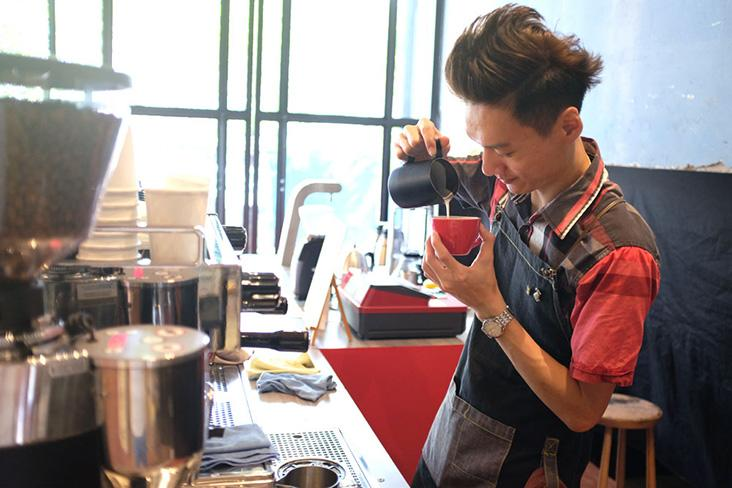 Barista pouring latte art at PPP Coffee's REXKL pop-up.