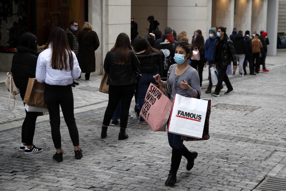 Youths stand in a queue as they wait to enter a clothes shop on Ermou Street, Athens' main shopping area, Friday, Jan. 22, 2021. Greece's government has extended nationwide lockdown measures indefinitely but retail stores and malls reopened Monday with strict entrance limits. (AP Photo/Thanassis Stavrakis)