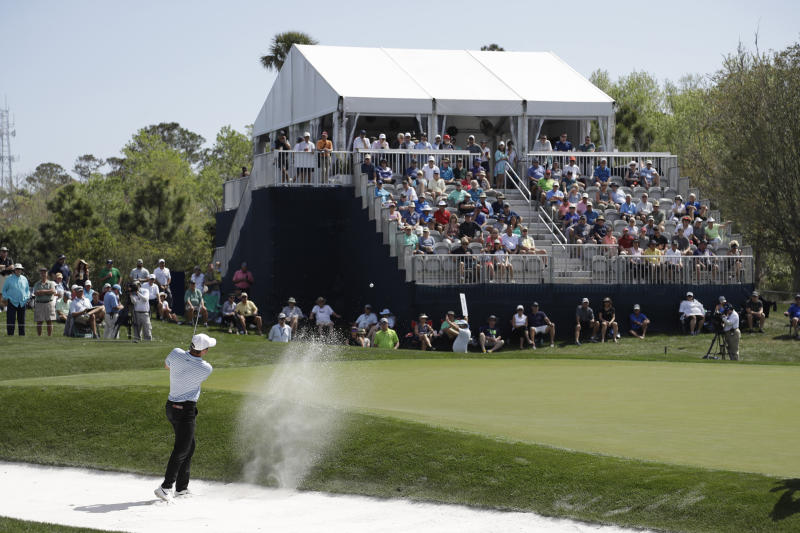 A small crowd watches Scottie Scheffler hit from the sand on the eighth hole, during the first round of The Players Championship golf tournament Thursday, March 12, 2020, in Ponte Vedra Beach, Fla. (AP Photo/Chris O'Meara)