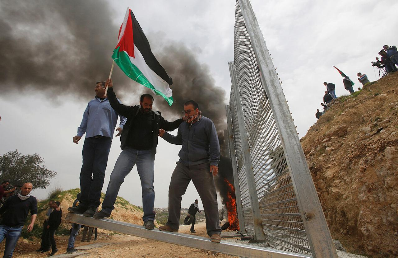 <p>Palestinian demonstrators try to remove a section of the Israeli barrier fence during a protest marking Land Day in the West Bank city of Beit Jala, March 30, 2017. Land Day commemorates the killing of six Arab citizens of Israel by the Israeli army and police on March 30, 1976 during protests over Israeli confiscations of Arab land. (Mussa Qawasma/Reuters) </p>