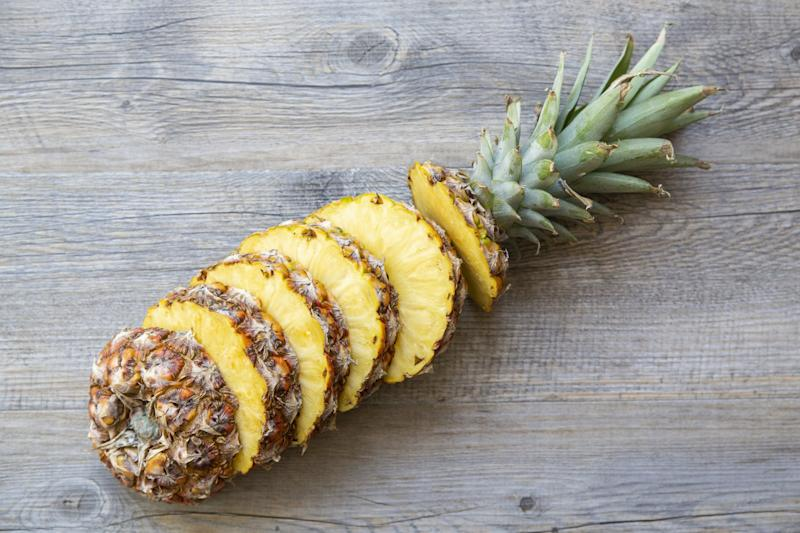Whole sliced pineapple on a wood background.