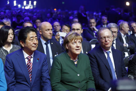 Japanese Prime Minister Shinzo Abe (L-R), German Chancellor Angela Merkel and Stephan Weil Lower Saxony attend the opening ceremony of the CeBit computer fair, which will open its doors to the public on March 20, at the fairground in Hanover, Germany, March 19, 2017.     REUTERS/Morris Mac Matzen
