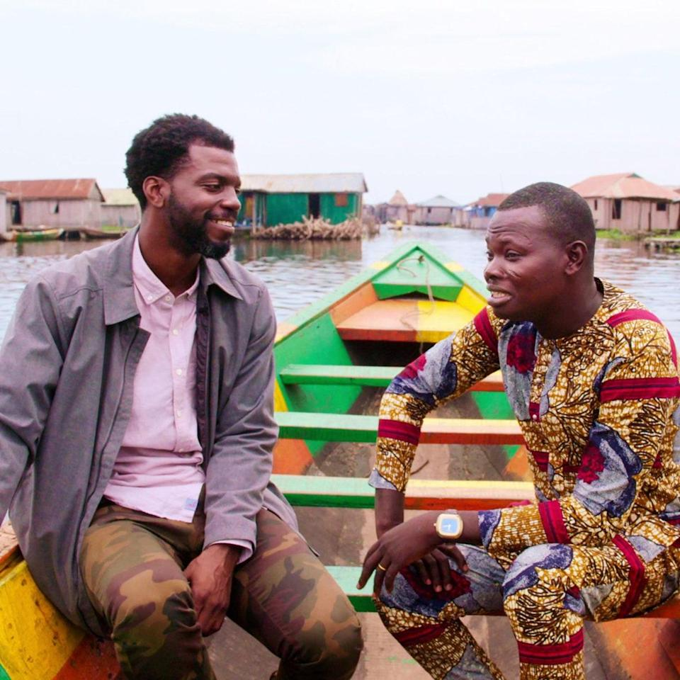 Satterfield (left) learns the history of Ganvié, Benin from local tour guide Eric Kiki.