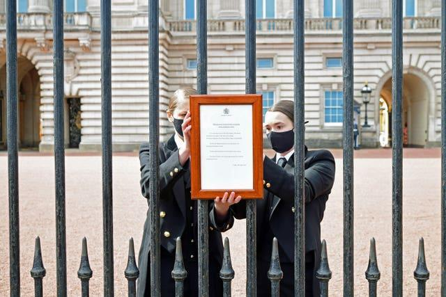 A sign announcing the death of the Duke of Edinburgh, who has died at the age of 99, is placed on the gates of Buckingham Palace, London (Ian West/PA)