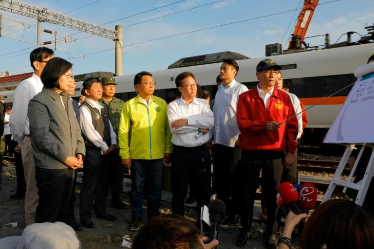 Rescue personnel from the fire department brief Taiwan's President Tsai Ing-wen (L) on their rescue efforts at Xinma station
