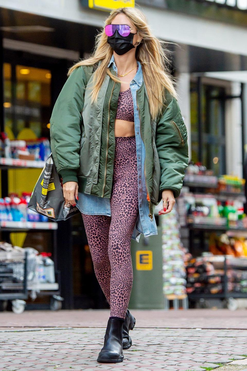 <p>Heidi Klum wears a green bomber jacket over a leopard-print workout set to go grocery shopping with her mom Erna in Berlin on Wednesday. </p>