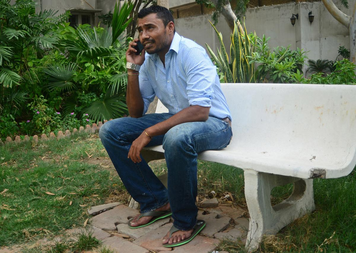Pakistani cricketer Danish Kaneria talks on his mobile phone outside his apartment in Karachi on July 5, 2013. Pakistan on July 5 endorsed England's decision to uphold the life ban on Danish Kaneria, calling on the leg-spinner to reflect on his conduct and start a process of rehabilitation. The 32-year-old was banned for his part in a 2009 spot-fixing scandal, in which he lured his Essex team-mate Mervyn Westfield to concede an agreed number of runs in an over in return for money. AFP PHOTO / RIZWAN TABASSUM