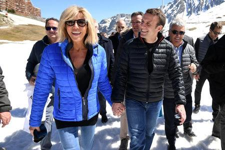 Emmanuel Macron (R), head of the political movement En Marche ! (Onwards !) and candidate for the 2017 presidential election, and his wife Brigitte Trogneux arrive for a lunch break at the mountain top during a campaign visit in Bagneres de Bigorre, in the Pyrenees mountain, France, April 12, 2017.  REUTERS/Eric Feferberg/Pool