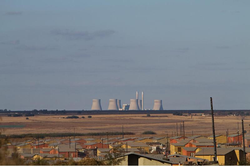 The cooling towers of a power plant are pictured from the township of Telmas, a suburb of Johannesburg on July 4, 2010