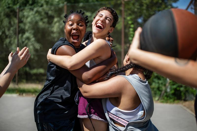 Multi-ethnic females celebrating a victory on basketball court. Women basketball team embracing each other and laughing after winning the match.