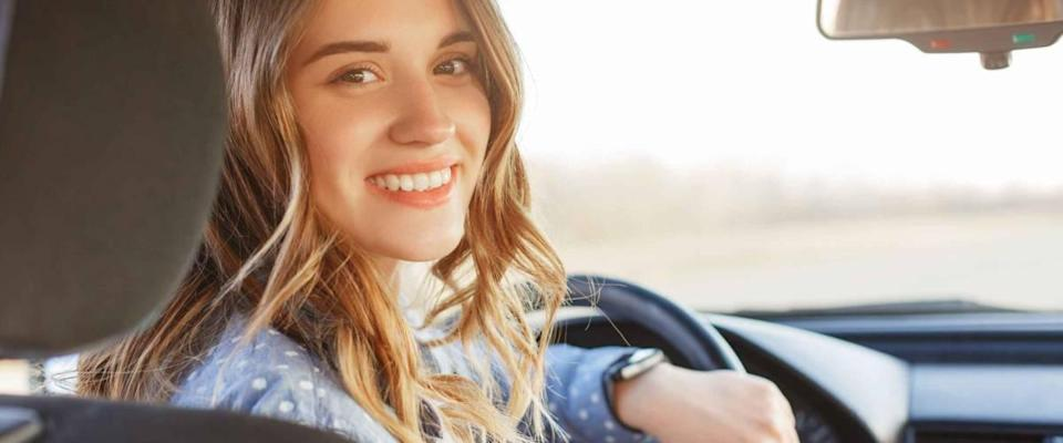 Young woman in the driver's seat, turned around and smiling into backseat