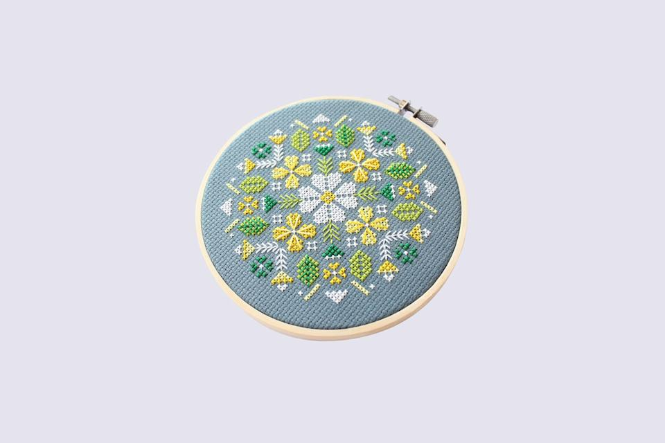 """<p>Canadian artist Diana Watters is famous for her cheery designs and bright colorwork. This pattern—stitched in yellow and green on slate blue Aida—is inspired by alpine flowers on a sunny day.</p> <p><strong><em>Shop Now:</em></strong><em> Diana Watters Handmade Alpine Flowers Cross Stitch Kit, $28, <a href=""""https://www.awin1.com/cread.php?awinmid=6220&awinaffid=272513&clickref=MSL10ofOurFavoriteCrossStitchKitsforBeginnersaharperDIYGal7998715202010I&p=https%3A%2F%2Fwww.etsy.com%2Flisting%2F698316738%2Falpine-flowers-modern-cross-stitch-kit"""" rel=""""nofollow noopener"""" target=""""_blank"""" data-ylk=""""slk:etsy.com"""" class=""""link rapid-noclick-resp"""">etsy.com</a></em><em>.</em></p>"""