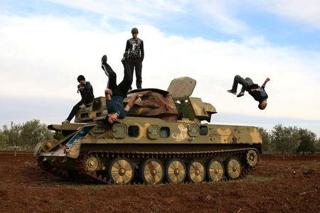 Muhannad al-Kadiri (R),18, and Ibrahim Eid, 16, demonstrate their Parkour skills over a military vehicle in the rebel-held city of Inkhil, west of Deraa, Syria, February 4, 2017. REUTERS/Alaa Al-Faqir