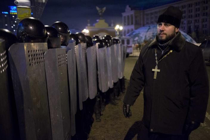 """An Ukrainian priest speaks to Riot police as they block Pro-European Union activists camping out in their tents on the Independence Square in Kiev, Ukraine, Wednesday, Dec. 11, 2013. Hundreds of police have moved on a large protest camp in the center of Kiev. Protesters are shouting """"Shame!"""" """"We will stand!"""" and singing the Ukrainian national anthem.(AP Photo/Alexander Zemlianichenko)"""