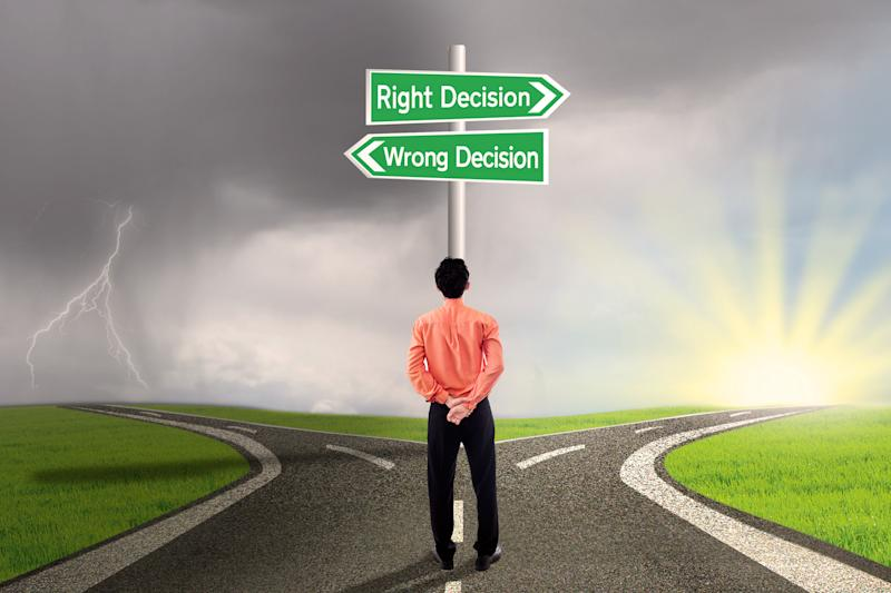 "e road with signs reading ""Right Decision"" and ""Wrong Decision""Man standing at a fork in th"