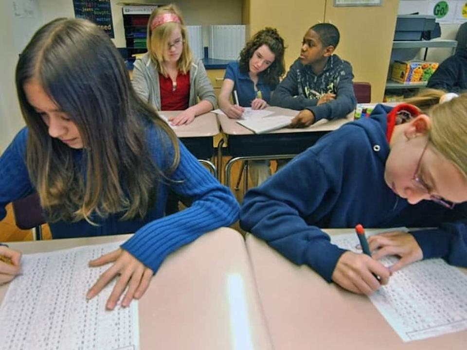 A new report suggests literacy scores for the EQAO standardized test, which students are seen taking here, are inflated by the use of technology. (The Canadian Press - image credit)