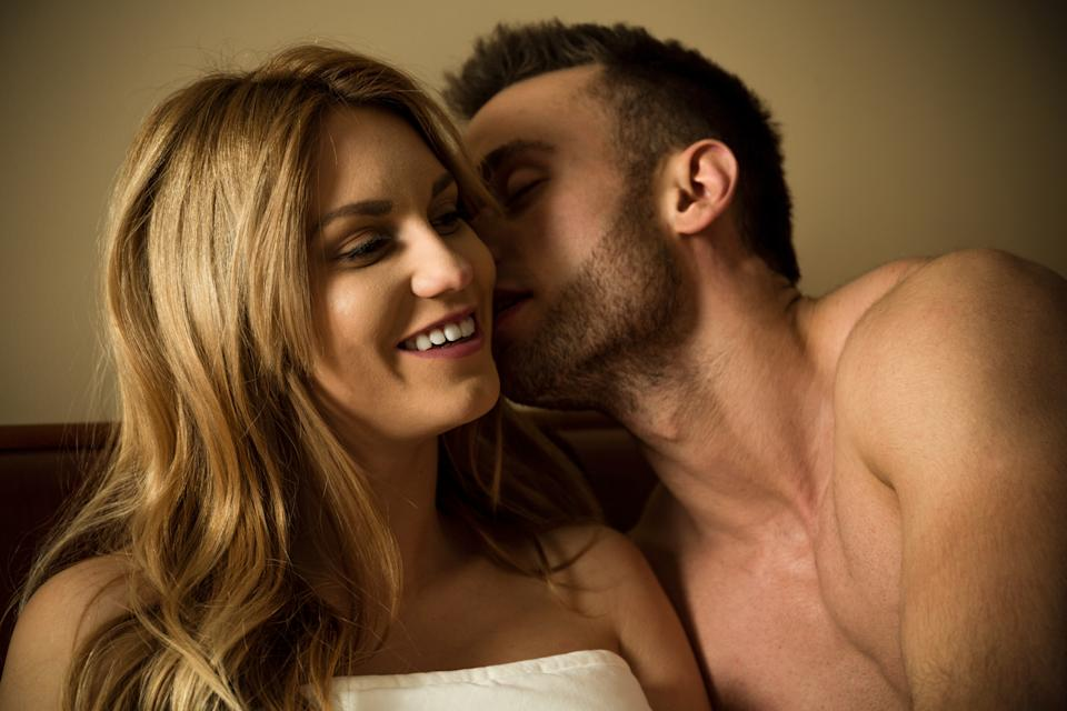 Man whispers to woman who looks pleased in bed