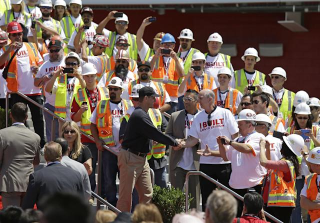 San Francisco 49ers head coach Jim Harbaugh shakes hands with construction workers just before the ribbon-cutting and opening of Levi's Stadium Thursday, July 17, 2014, in Santa Clara, Calif. The San Francisco 49ers held a ribbon-cutting ceremony to officially open their new home. The $1.2 billion Levi's Stadium, which took only about 27 months to build, also will host the NFL Super Bowl in 2016 and other major events. (AP Photo/Eric Risberg)