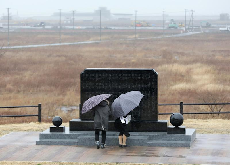 A couple prays in front of a memorial monument in Namie, Fukushima Prefecture, on the eighth anniversary of the 2011 tsunami disaster (AFP Photo/JIJI PRESS)