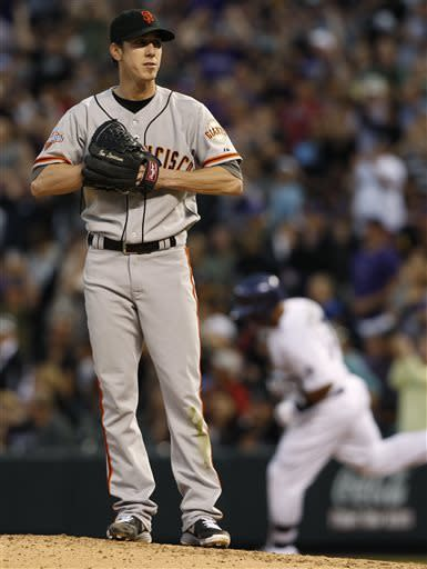 San Francisco Giants starting pitcher Tim Lincecum, foreground, reacts as Colorado Rockies' Wilin Rosario, background, rounds the bases after hitting a two-run home run in the fifth inning of a baseball game in Denver, Saturday, May 18, 2013. (AP Photo/David Zalubowski)