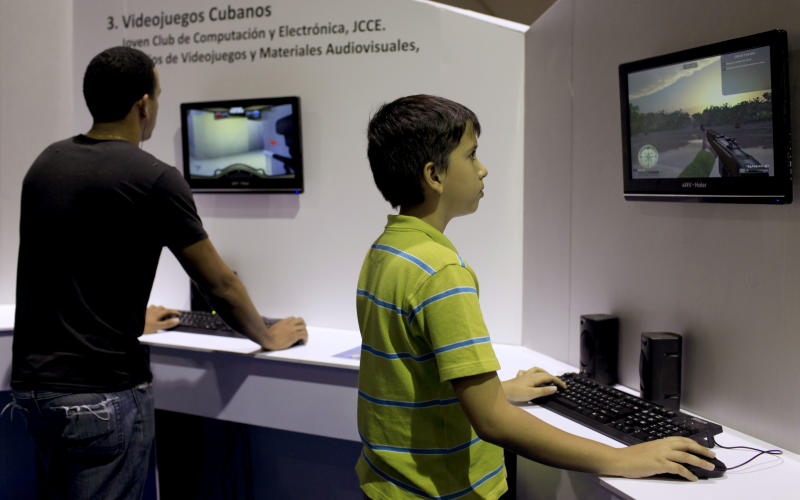 "In this March 22, 2013 photo, Rogelio Garcia, 10, right, plays the video game, ""Gesta Final"" - which translates roughly as ""Final Heroic Deed,"" at a technology fair in Havana, Cuba. Island programmers have unveiled the brand new 3-D shoot-'em-up video game that puts a distinctly Cuban twist on gaming, letting players recreate decisive clashes from the 1959 revolution and giving youngsters a taste of the uprising in which many of their grandparents fought. (AP Photo/Franklin Reyes)"