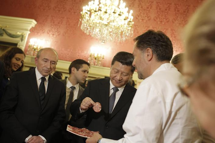 Chinese President Xi Jinping, center, tastes local food during a visit before a dinner at the town hall in Lyon, central France, Tuesday, March 25, 2014. Xi Jinping arrived in France for a three-day state visit. (AP Photo/Laurent Cipriani, Pool)