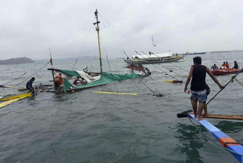 In this photo provided by the Philippine Red Cross, rescuers checks the remains of a ferry boat after it capsized due to bad weather in the waters between Guimaras and Iloilo provinces, central Philippines on Saturday Aug. 3, 2019. Several people died and 31 others were rescued when three ferry boats separately capsized in bad weather Saturday between two central Philippine island provinces, the coast guard said. (Philippine Red Cross via AP)