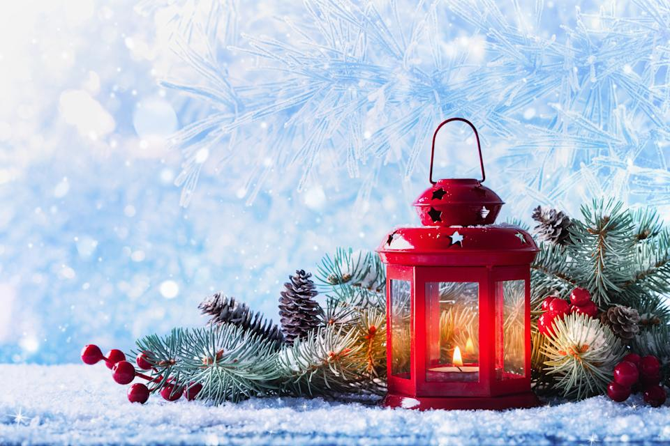 Christmas lantern in snow with fir tree branch and decorations. Winter cozy scene for New Year holidays.