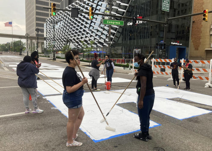 """Students from University Prep Art Design celebrate Juneteenth by repainting a street mural, """"Power To The People,"""" in downtown Detroit on Saturday, June 19, 2021. (AP Photo/Ed White)"""