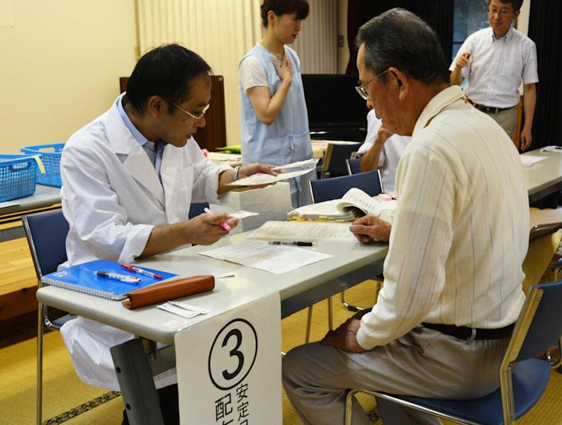 A local resident (right) receives iodine tablets from a Kagoshima prefectural officer in Satsumasendai, on Japan's southern island of Kyushu, on July 27, 2014 (AFP Photo/)