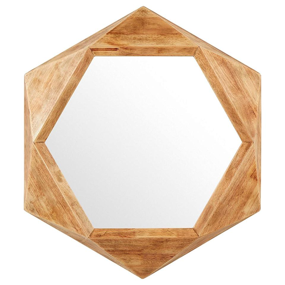 "<p>The pretty wood detail on this <a href=""https://www.popsugar.com/buy/Rivet%20Modern%20Hexagon%20Wood%20Frame%20Mirror-449572?p_name=Rivet%20Modern%20Hexagon%20Wood%20Frame%20Mirror&retailer=amazon.com&price=100&evar1=casa%3Aus&evar9=46178542&evar98=https%3A%2F%2Fwww.popsugar.com%2Fhome%2Fphoto-gallery%2F46178542%2Fimage%2F46178868%2FRivet-Modern-Hexagon-Wood-Frame-Mirror&list1=amazon%2Cmirrors%2Cshoppping%2Chome%20shopping&prop13=api&pdata=1"" rel=""nofollow"" data-shoppable-link=""1"" target=""_blank"">Rivet Modern Hexagon Wood Frame Mirror</a> ($100) sold us.</p>"