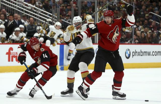 Arizona Coyotes right wing Richard Panik (14) skates around Vegas Golden Knights right wing Reilly Smith (19) and Coyotes defenseman Ilya Lyubushkin, right, to get to the puck during the first period of an NHL hockey game Sunday, Dec. 30, 2018, in Glendale, Ariz. (AP Photo/Ross D. Franklin)