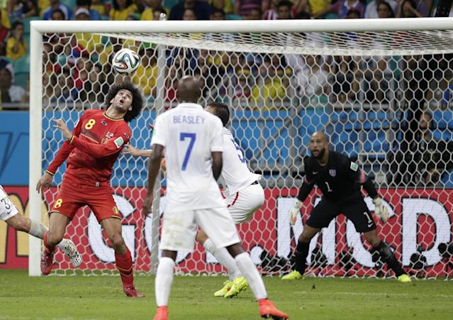 United States' goalkeeper Tim Howard, right, eyes the ball as Belgium's Marouane Fellaini (8) goes for a header during the World Cup round of 16 soccer match between Belgium and the USA at the Arena Fonte Nova in Salvador, Brazil, Tuesday, July 1, 2014. (AP Photo/Felipe Dana)