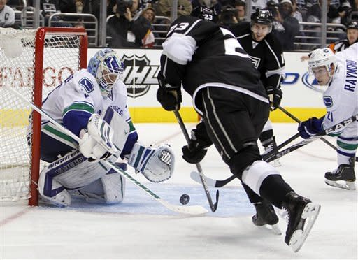 Vancouver Canucks goalie Cory Schneider (35) blocks a shot by Los Angeles Kings right wing Dustin Brown (23) during the second period of Game 3 in a first-round NHL Stanley Cup playoff series in Los Angeles, Sunday, April 15, 2012. (AP Photo/Alex Gallardo)