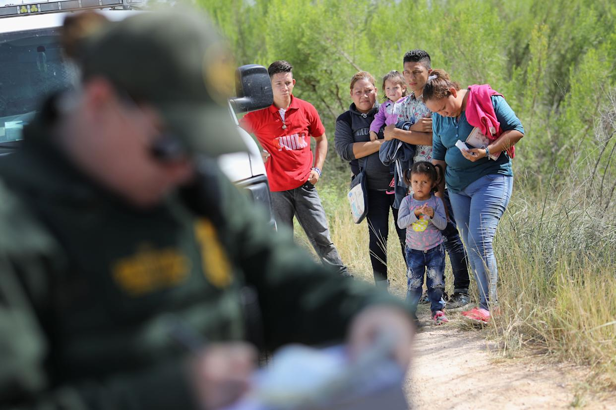 Central American migrants wait as U.S. Border Patrol agents take people into custody on June 12, 2018, near McAllen, Texas.
