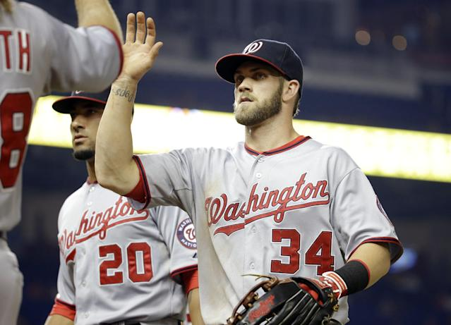 Washington Nationals' Bryce Harper (34) is congratulated by Jayson Werth, left, after throwing to the infield to get Miami Marlins' Jarrod Saltalamacchia out at second to end the fifth inning during a baseball game, Monday, July 28, 2014, in Miami. (AP Photo/Lynne Sladky)