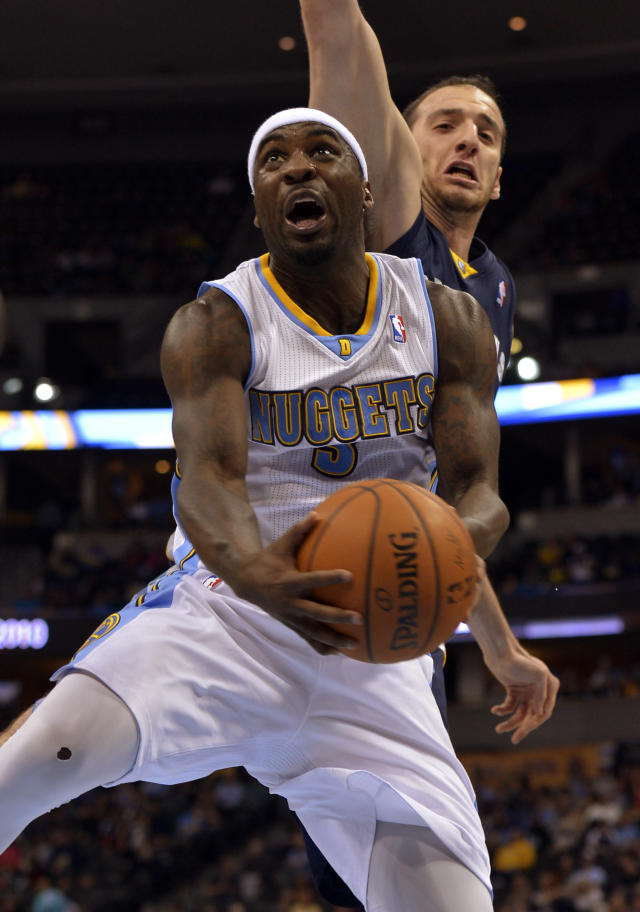 Denver Nuggets guard Ty Lawson, front, goes up for a shot against Memphis Grizzlies center Kosta Koufos during the third quarter of an NBA basketball game on Monday, March 31, 2014, in Denver. (AP Photo/Jack Dempsey)