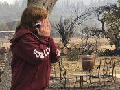 "FILE - In this Sept. 30, 2020, file photo, Nikki Conant cries as she looks at the debris of her home and business, ""Conants Wine Barrel Creations,"" after the Glass/Shady fire completely engulfed it in Santa Rosa, Calif. A new generation of California voters is being asked to roll back affirmative action and property tax laws put in place decades ago in an election that will test the boundaries of the state's left-leaning politics. Voters are being asked to unspool part of landmark Proposition 13, the 1970s law that set strict limits on property tax increases and fueled a national tax revolt. (AP Photo/Haven Daley, File)"