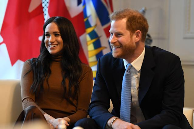 Britain's Prince Harry, Duke of Sussex and Meghan, Duchess of Sussex react during their visit to Canada House in thanks for the warm Canadian hospitality. [Photo: Getty]