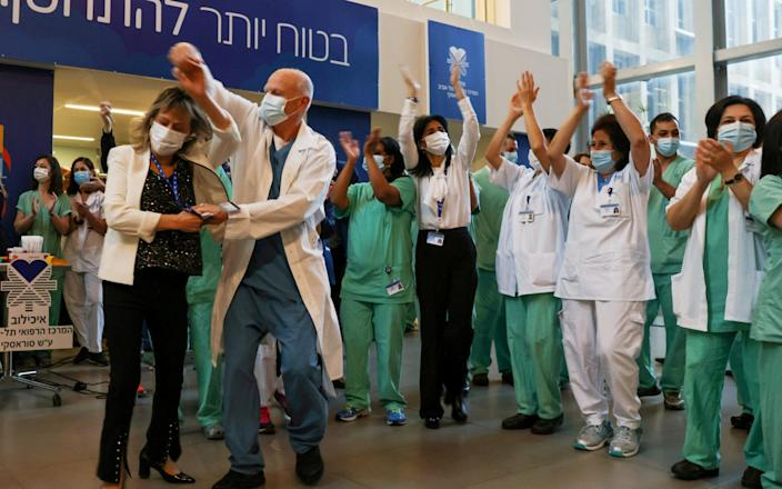 Medical teams celebrate before receiving coronavirus vaccines as Israel kicks off its coronavirus vaccination drive, at Tel Aviv Sourasky Medical Center - Ronen Zvulun/Reuters
